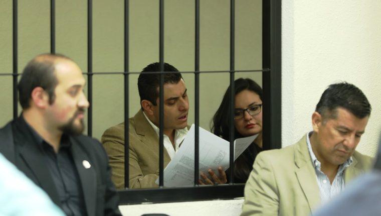 René Arturo Morales y su esposa Carmen Barrientos Salguero, yerno e hija del exalcalde de Xela, leen la acusación que les hace la Fiscalía Especial contra la Impunidad. (Foto Prensa Libre: Mynor Toc)