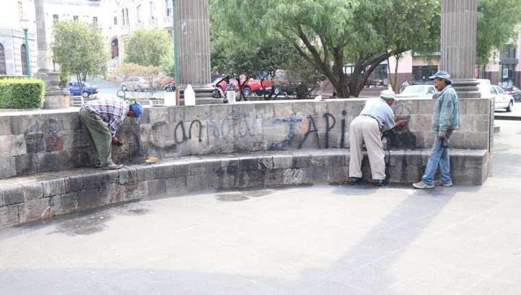 Trabajadores de la municipalidad limpian diferentes pintas en el parque central de Xela. (Foto Prensa Libre: María José Longo).