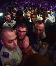 Khabib Nurmagomedov gana la pelea a McGregor y sale protegido por los incidentes al final de la pelea. (Foto Prensa Libre: AFP)