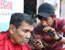 Rolando Fernández corta el cabello a Julio Jiménez, en Mazatenango. (Foto Prensa Libre: Cristian I. Soto)
