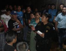 Agente de la PNC dialoga con pobladores, quienes se opusieron al traslado del cadáver de recién nacido en Panzós. (Foto Prensa Libre: Eduardo Sam).