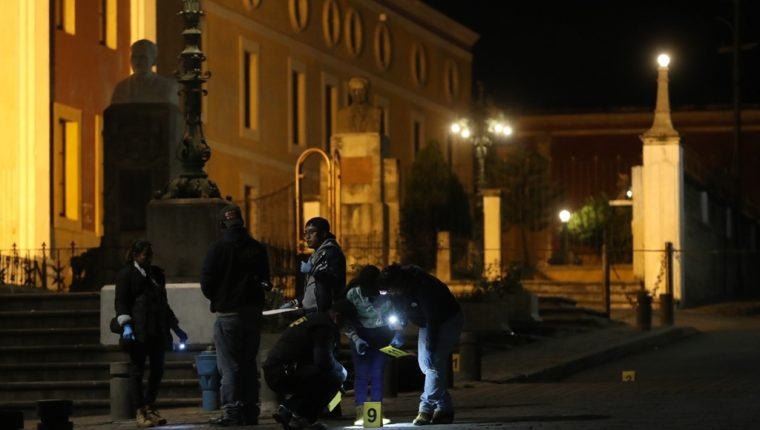 Investigadores del Ministerio Público revisan el área donde la noche del sábado un hombre de 20 años fue ultimado a balazos frente al Teatro Municipal. (Foto Prensa Libre: Mynor Toc)