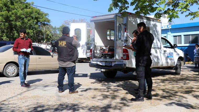 Fiscales del MP y agentes de la PNC resguardan la ambulancia donde murió el trabajador municipal. (Foto Prensa Libre: Mario Morales)