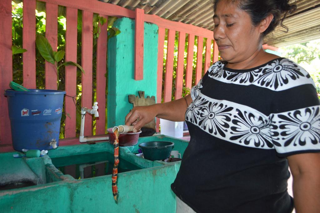 Vecina muestra una de las serpientes localizadas en una tubería. (Foto Prensa Libre: Oswaldo Cardona).