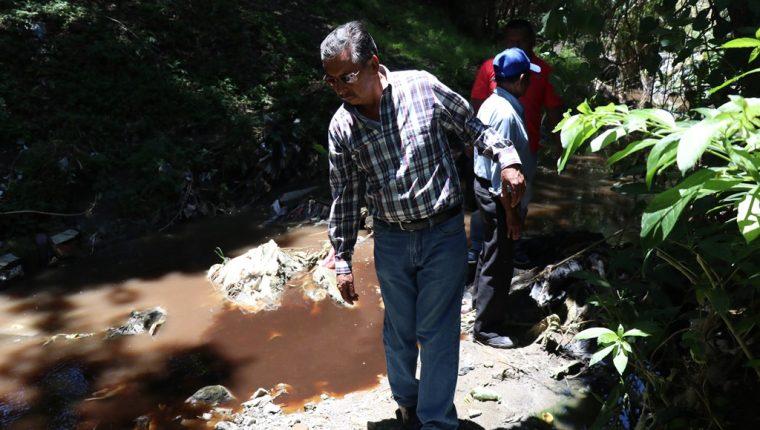 Un vecino observa el río de aguas servidas teñido de café, en la colonia Minerva, zona 2, Huehuetenango. (Foto Prensa Libre: Mike Castillo)