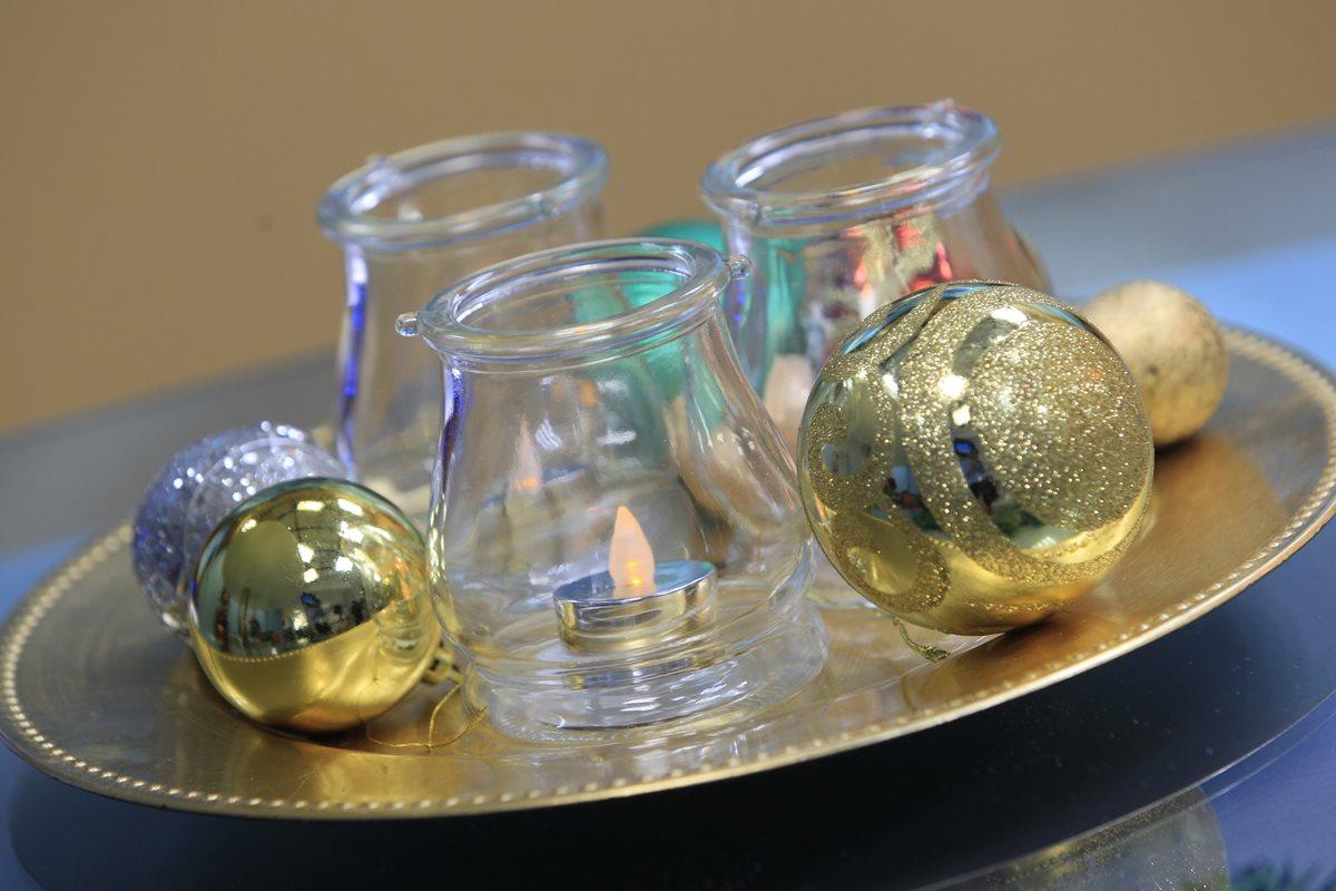 El dorado y el plateado son colores que siempre han caracterizado la decoración navideña. Este centro de mesa —sobre una base color oro— incluye bombas y vasos de cristal con velas con luz artificial en el interior. (Fotos Prensa Libre, Carlos Hernández)