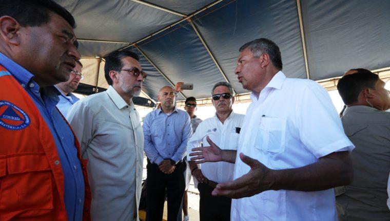 Los embajadores en Guatemala de EE. UU., Luis Arreaga (i) y de México, Manuel López (d), hablan durante una improvisada reunión en el paso fronterizo de Tecún Umán. (Foto Prensa Libre: Mynor Toc)