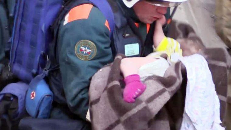 Oficiales de emergencia que transportan a un bebé sobreviviente después de una explosión de gas que sacudió un edificio residencial en la ciudad de los Urales, en Rusia, en Magnitogorsk. (Foto Prensa Libre: AFP
