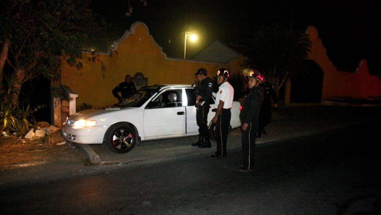Agentes de la PNC y Bomberos Voluntarios observan el vehículo en el que quedaron los cadáveres de las víctimas. (Foto Prensa Libre: Renato Melgar)