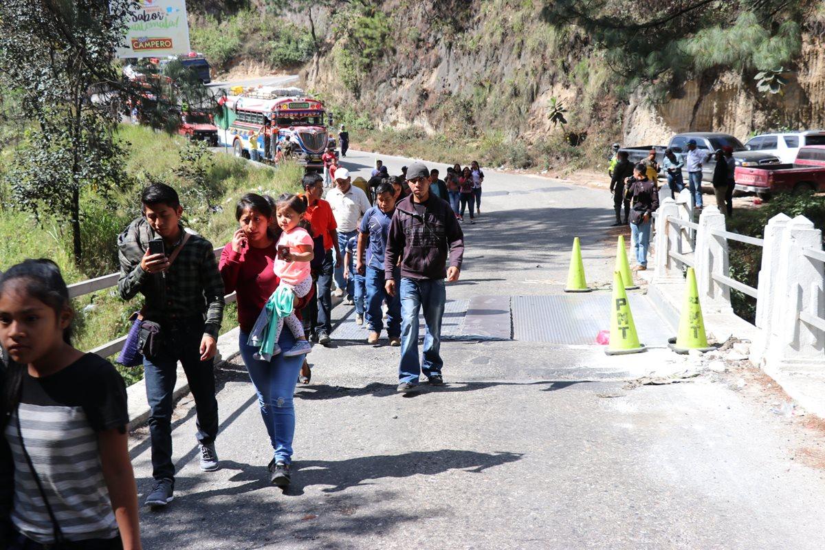 Los pasajeros de los buses extraurbanos son obligados a bajarse de las unidades para pasar a pie sobre el puente. (Foto: Prensa Libre: Héctor Cordero).