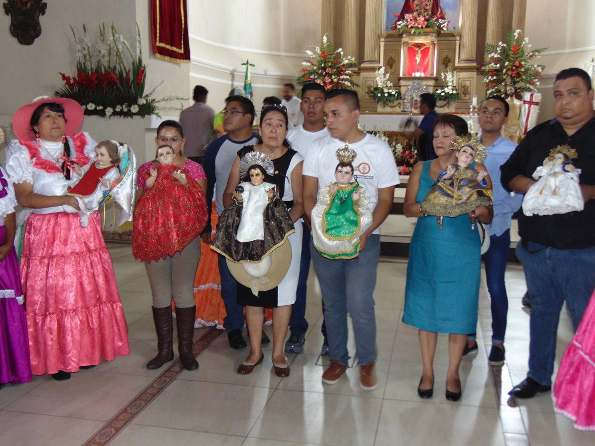 Peregrinos llevan hacia la parroquia de San Juan Bautista de Amatitlán las imágenes de niños visitantes, como parte de la celebración de la Feria en honor de la Santa Cruz.(Foto Prensa Libre: Cortesía)