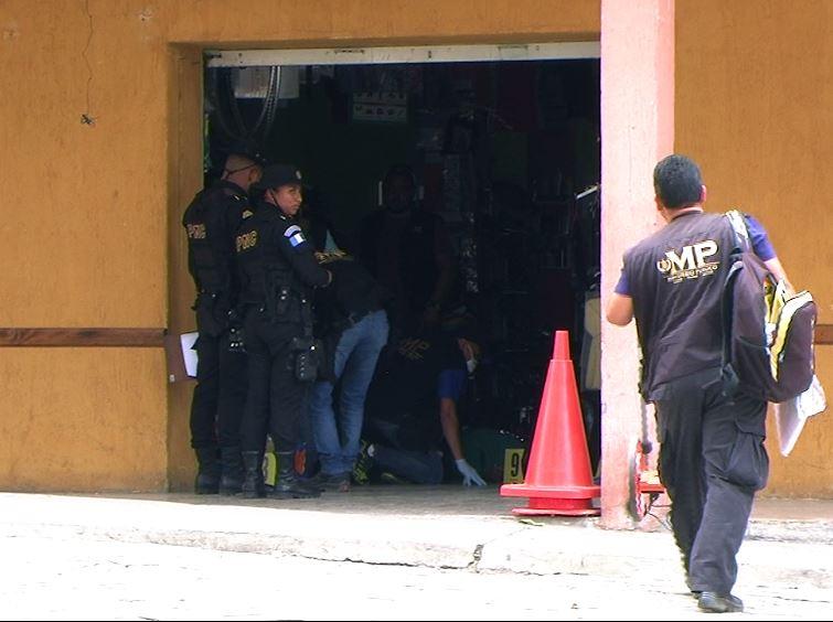 Fiscales del MP y agentes policiales trabajan dentro de la librería donde fue ultimado el líder campesino. (Foto Prensa Libre: Hugo Oliva)