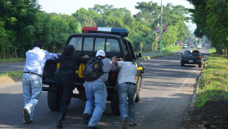 Policías y civiles empujan una autopatrulla con fallos mecánicos. (Foto Prensa Libre: Hemeroteca PL)