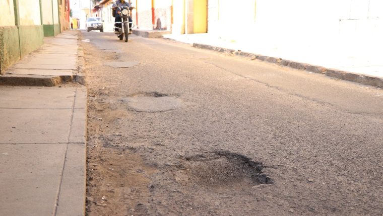 Calles de la zona 1 de Quetzaltenango son las más afectadas por agujeros, que afectan el paso vehicular. (Foto Prensa Libre: María José Longo).