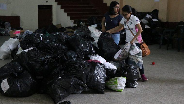 Voluntarias ayudan a clasificar los productos que se encuentran en el centro de acopio de Quetzaltenango. (Foto Prensa Libre: María José Longo)