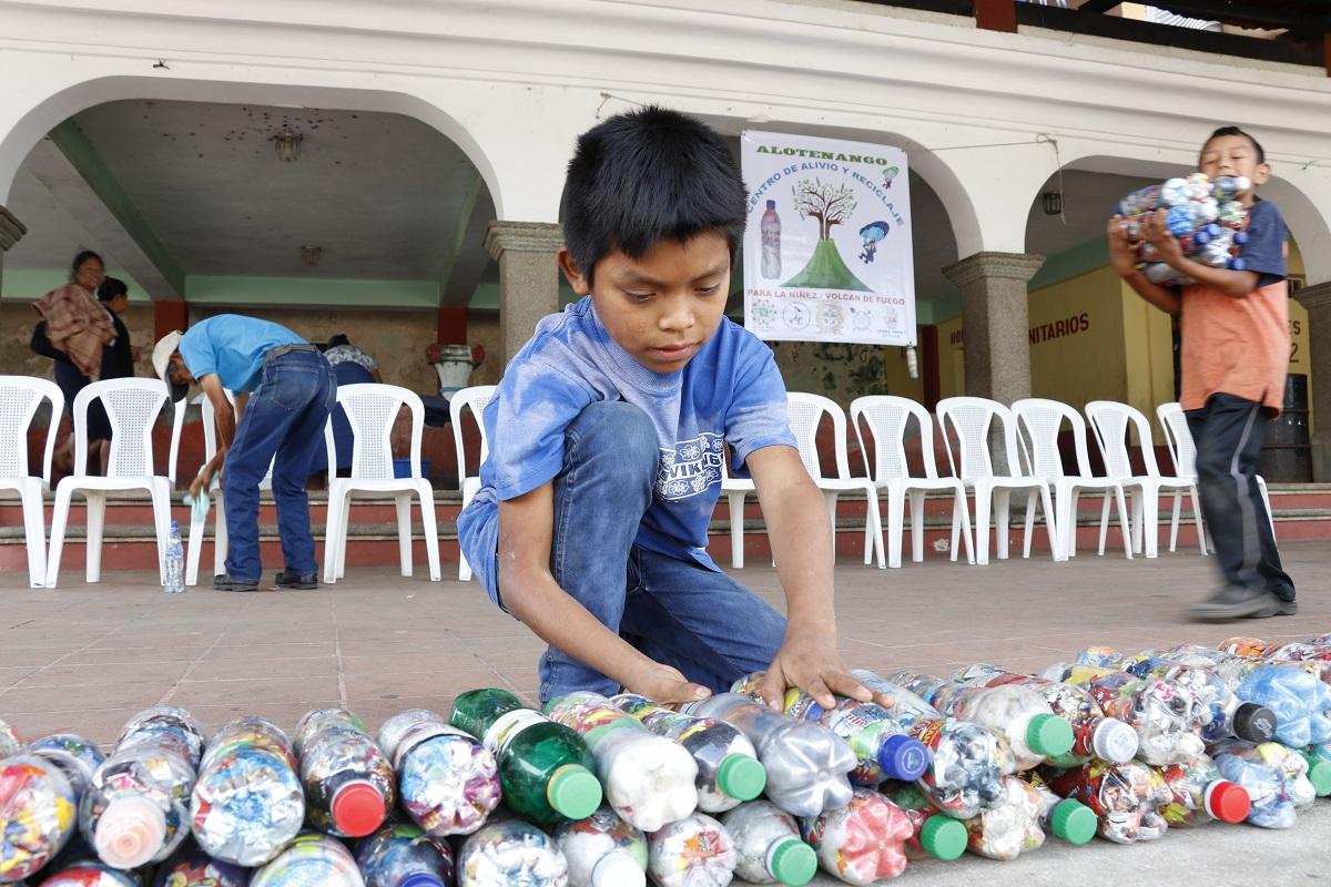 Niños de San Juan Alotenango ayudan a ordenar los ecoladrillos que serán utilizados para construir el módulo de lectura. (Foto Prensa Libre: Julio Sicán).