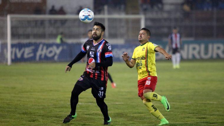Ricardo Rocha observa el balón con la marca de Jonathan Pérez. (Foto Prensa Libre: Carlos Ventura)