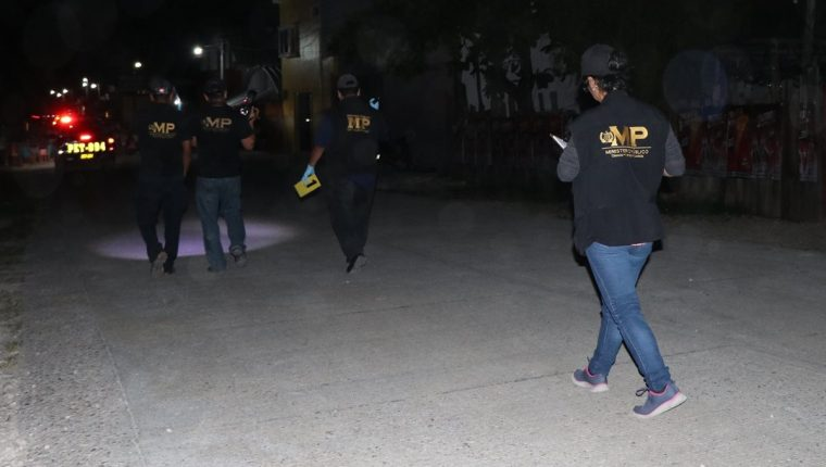 Investigadores se dirigen al lugar donde fue ultimada a balazos una pareja en el área urbana de San Benito. (Foto Prensa Libre: Rigoberto Escobar).