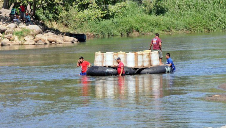 Una balsa transportando recipientes con combustible atraviesa el Suchiate hacia territorio mexicano. (Foto Prensa Libre: Alexander Coyoy)