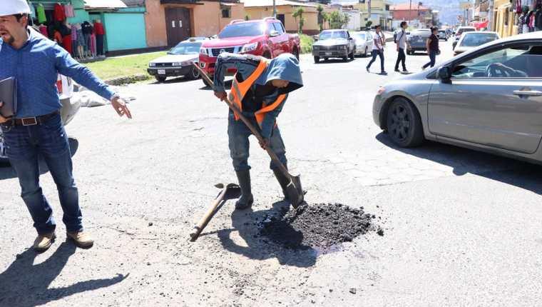 Trabajadores municipales aplican emulsión asfáltica en frío para rellenar hoyos en calles de la zona 3 de Xela. (Foto Prensa Libre: María José Longo).