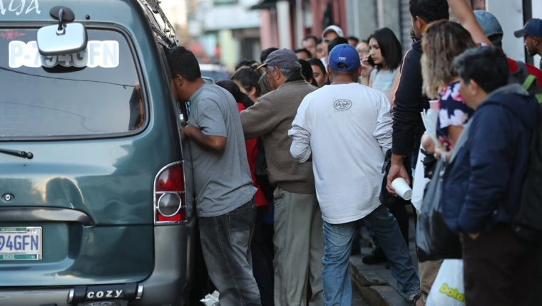 Ayudante del microbús ordena pasajeros en el vehículo ante la demanda para el traslado a la zona 18. (Foto Prensa Libre: Érick Ávila)