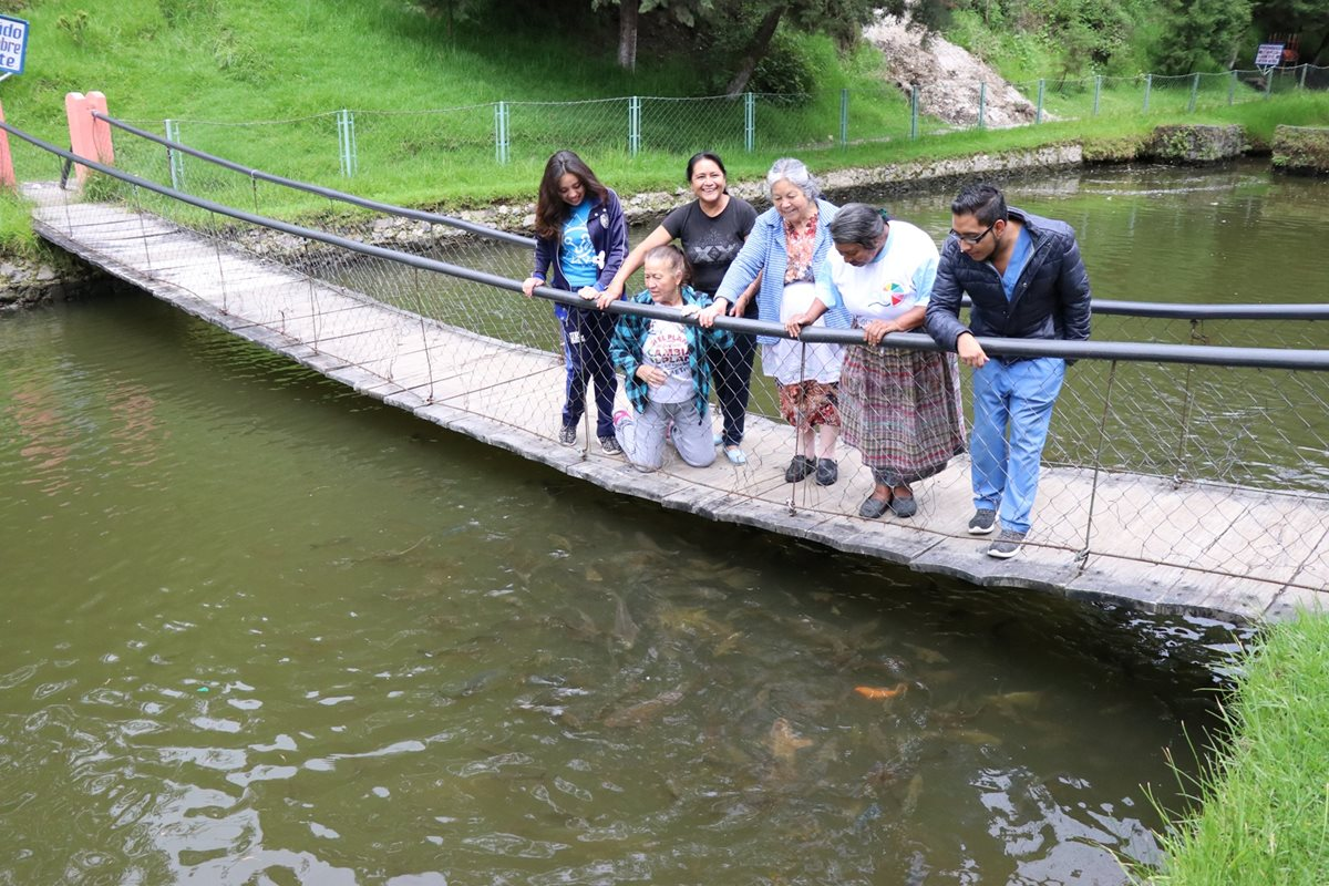 Turistas observan los peces de la laguneta que le da nombre al sitio turístico de Salcajá. (Foto Prensa Libre: María José Longo)