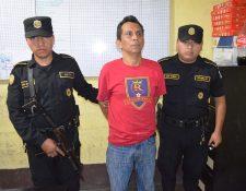 Agentes de la PNC custodian a presunto violador, en San Felipe, Retalhuleu. (Foto Prensa Libre: Jorge Tizol)