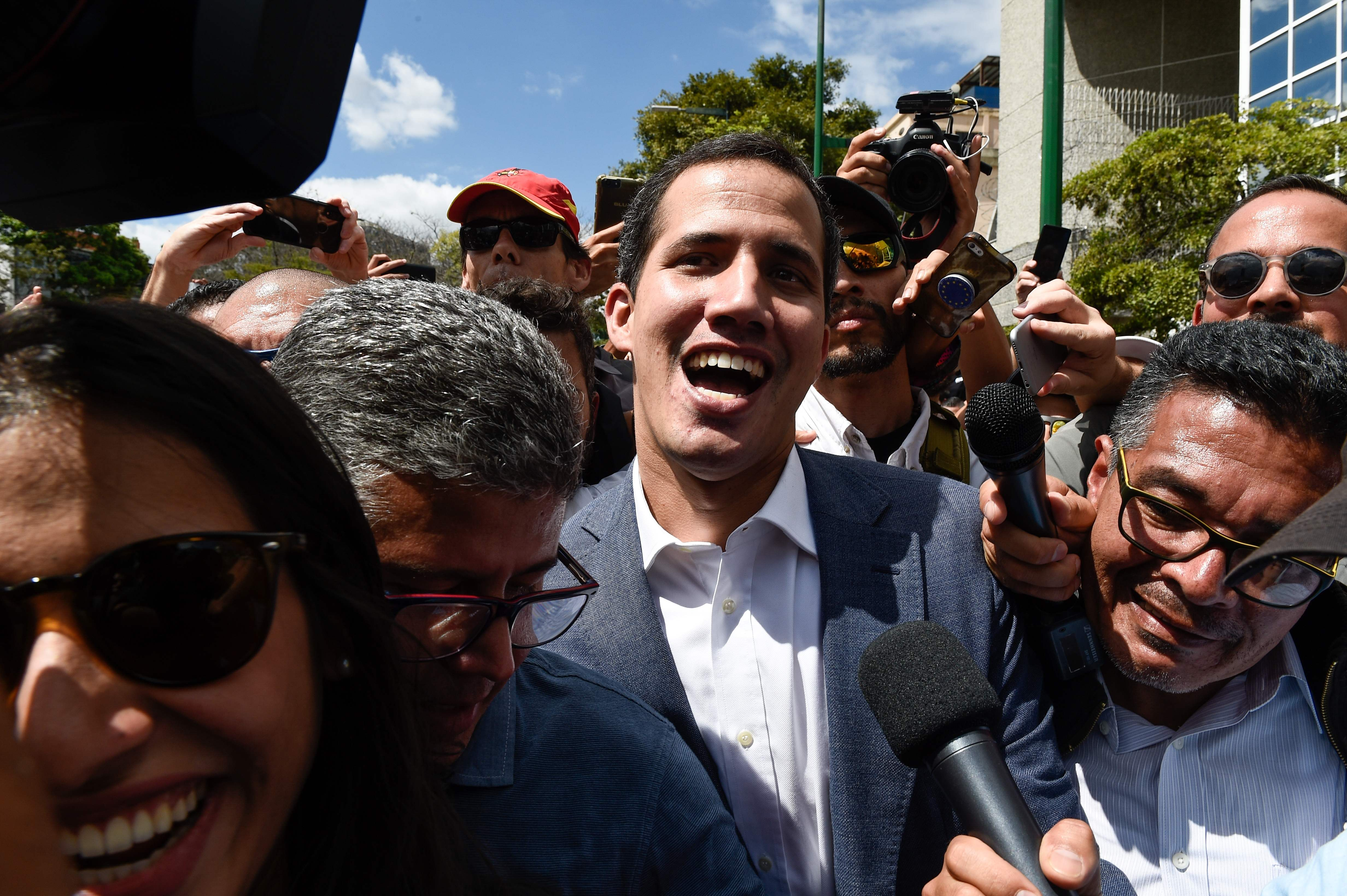 """The head of Venezuela's National Assembly and the country's self-proclaimed """"acting president"""" Juan Guaido (C) leaves after a rally with opposition supporters in Caracas, on January 26, 2019. (Photo by Federico PARRA / AFP)"""