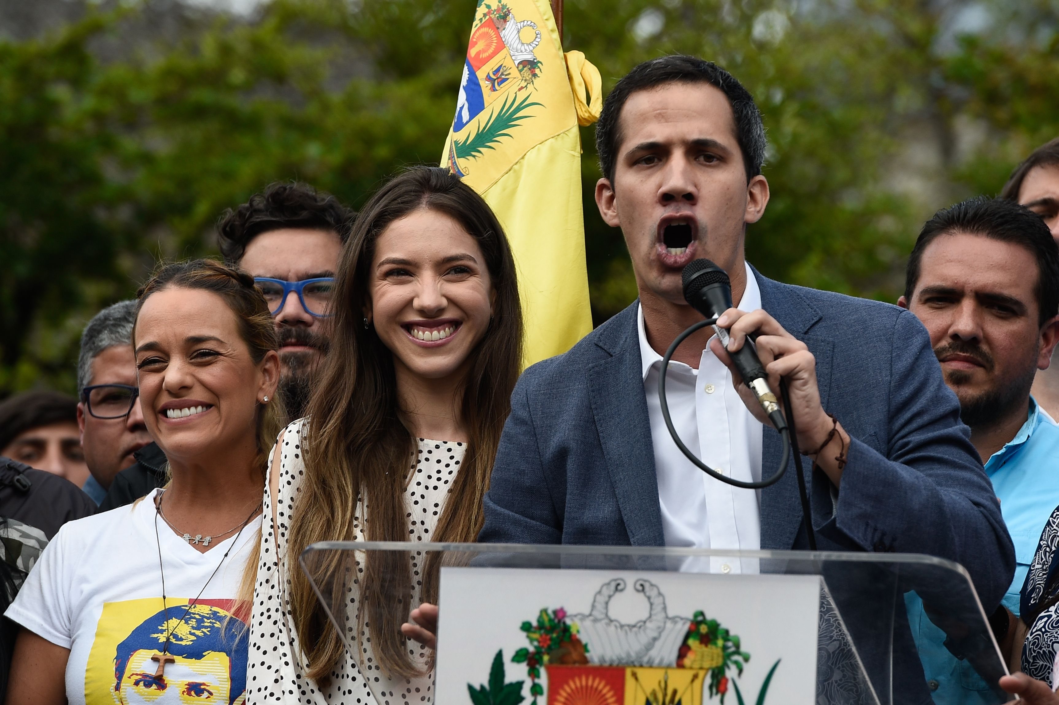 "The head of Venezuela's National Assembly and the country's self-proclaimed ""acting president"" Juan Guaido (R) speaks next to his wife Fabiana Rosales (C) and activist Lilian Tintori (L), wife of Venezuelan opposition leader Leopoldo Lopez, to a crowd of opposition supporters in Caracas, on January 26, 2019. (Photo by Federico PARRA / AFP)"