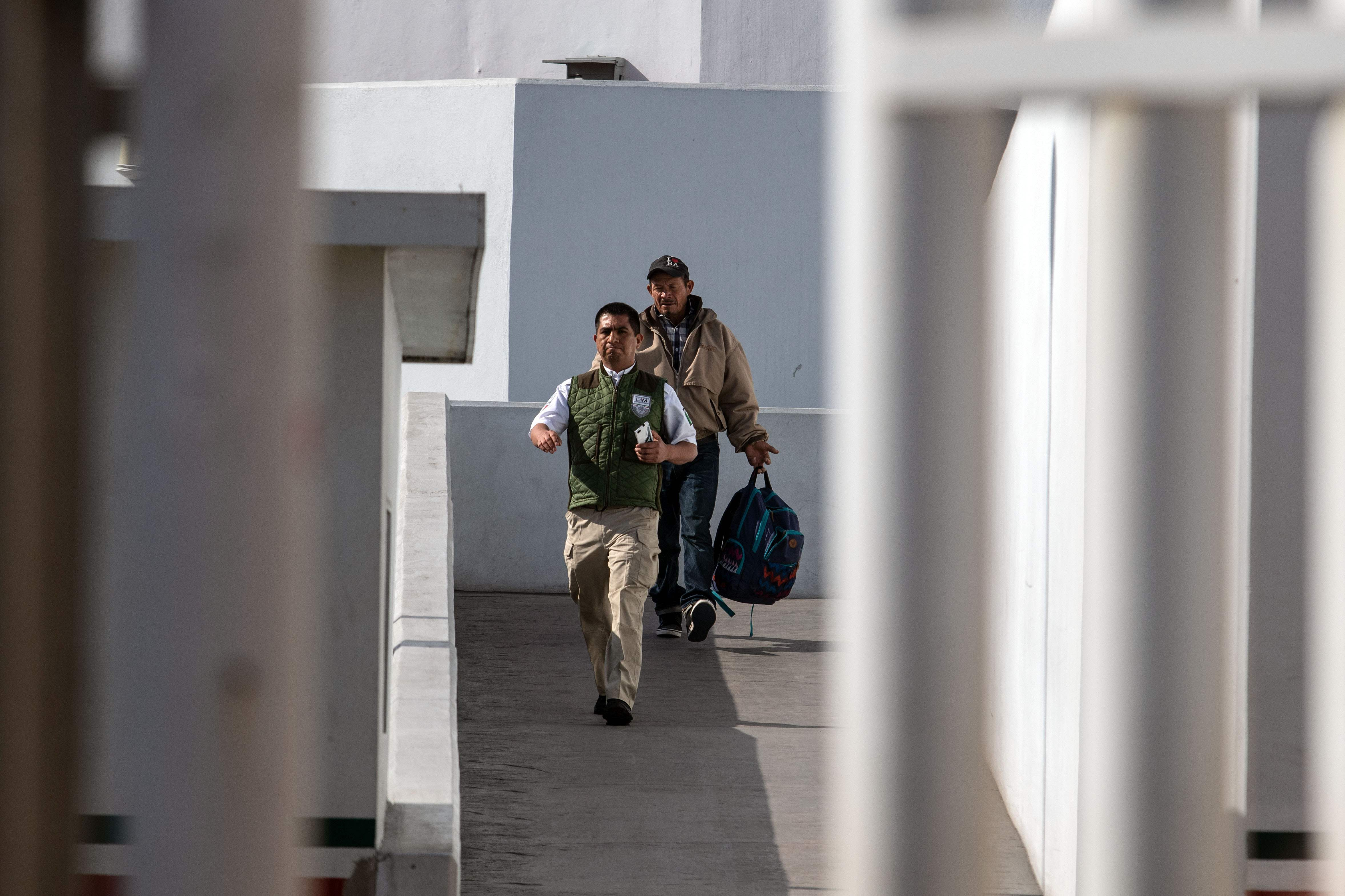 Carlos Catarlo Gomez, an asylum seeker from Honduras, returns to Mexico from the United States while his case is processed by US authorities, at El Chaparral crossing port on the US-Mexico border, in Tijuana, Baja California state, Mexico, on January 29, 2019. - According to Mexico's National Migration Institute, Carlos is the first migrant returned by US authorities under the new Migration Protocol, under which the US sends asylum seekers back to Mexico while their claims are processed. (Photo by Guillermo Arias / AFP)