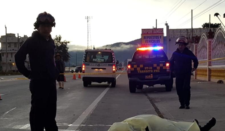 Bomberos observan al agente de la PNC que murió arrollado en la ruta Interamericana. (Foto Prensa Libre: Cortesía).