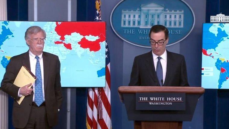"""AME5088. WASHINGTON (ESTADOS UNIDOS), 28/01/2019.- Captura de vídeo cedida por la Casa Blanca de una rueda de prensa del secretario del Tesoro de los Estados Unidos Steven Mnuchin (d) junto al asesor de seguridad nacional de Estados Unidos John Bolton (i) este lunes en la Casa Blanca en Washington (EE.UU.). Bolton tenía escrito en su cuaderno """"5.000 tropas a Colombia"""" durante la rueda de prensa en la que la Casa Blanca anunció sanciones contra la compañía estatal Petróleos de Venezuela (Pdvsa). En una ampliación de fotografías tomadas por diversos medios de comunicación durante la rueda de prensa se aprecian dos inscripciones en el cuaderno de Bolton: la primera reza """"Afganistán, bienvenidas las negociaciones"""" de paz con los talibanes, mientras que la segunda dice """"5.000 tropas a Colombia"""". EFE/CASA BLANCA/SOLO USO EDITORIAL/NO VENTAS"""