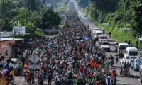 Una primera caravana de hondureños salió en octubre pasado. En la fotografía, migrantes se observan hacia territorio estadounidense desde la frontera de Tijuana, México. (Foto Prensa Libre: AFP)