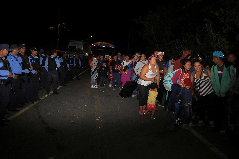AME8131. AGUA CALIENTE (HONDURAS), 15/01/2019.- Ciudadanos hondureños pasan por un reten policial hoy, en la aduana de Agua Caliente, frontera entre Honduras y Guatemala. Al menos 500 hondureños de la caravana de migrantes que salió el lunes de su país cruzó hoy la frontera con Guatemala, y tiene previsto continuar por el territorio para intentar llegar a Estados Unidos, pudo constatar Efe. Los migrantes hondureños, entre ellos varios menores de edad, pasaron este martes el punto fronterizo de Agua Caliente y se dirigen hacia Esquipulas.EFE/Gustavo Amador