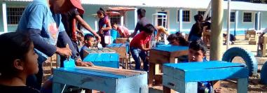 Un grupo de estudiantes fabrica escritorios con cajas para verdura. (Foto Prensa Libre: Eduardo Sam).