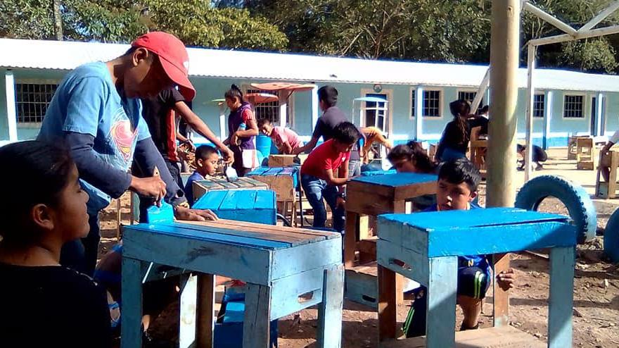 Niños estudian sobre cajas para verdura, maestro pide apoyo para obtener mobiliario