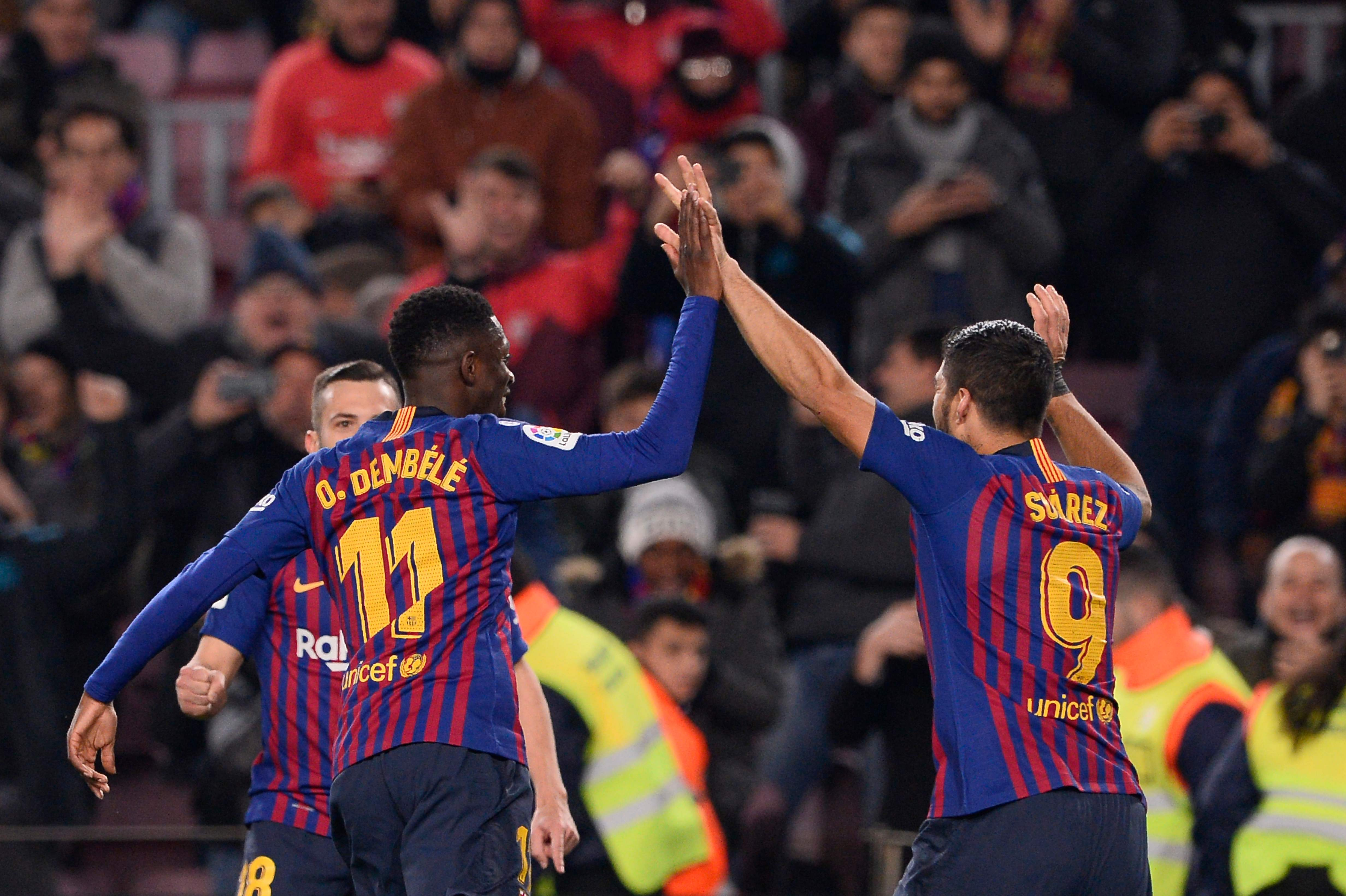 Barcelona's French forward Ousmane Dembele (C) celebrates with Barcelona's Uruguayan forward Luis Suarez after scoring during the Spanish League football match between Barcelona and Leganes at the Camp Nou stadium in Barcelona on January 20, 2019. (Photo by Josep LAGO / AFP)