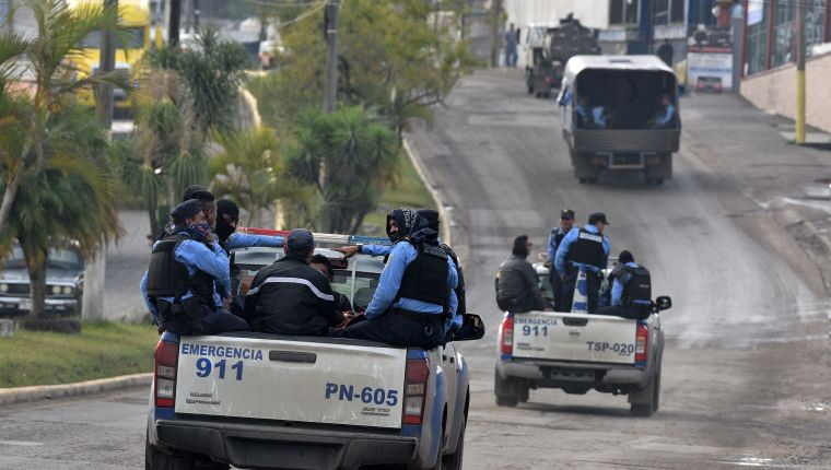 National Police forces ride through the streets of Santa Rosa de Copan, a municipality in western Honduras, on their way to El Poy on the border with El Salvador, where a second caravan of Honduran migrants wanting to reach the United States is heading, on January 15, 2019. - Hundreds of Hondurans have set out on a trek to the United States, forming another caravan that US President Donald Trump cited Tuesday to justify building a wall on the border with Mexico. (Photo by Orlando SIERRA / AFP)