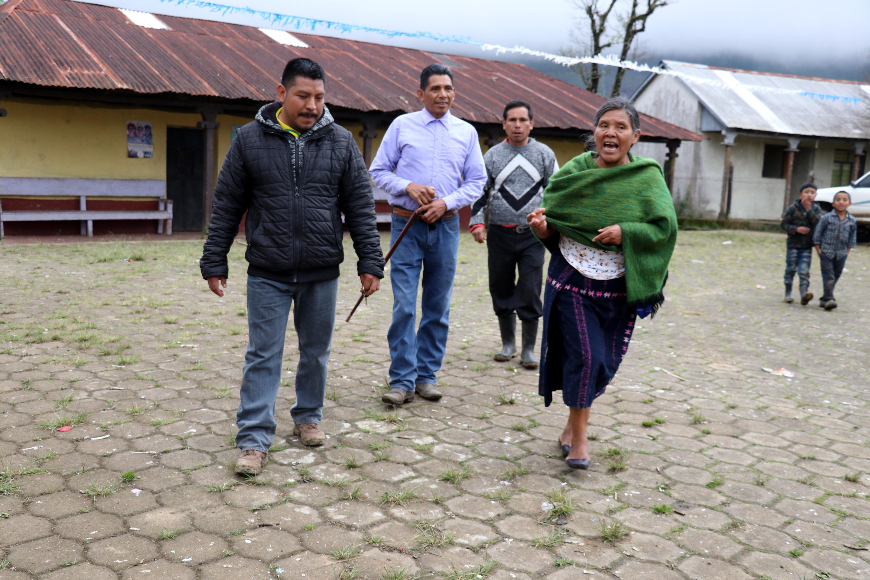 El maestro Felipe Gómez Domingo -con chumpa negra- narra la situación de la educación en la comunidad Yalambojoch, Nentón, Huehuetenango. (Foto Prensa Libre: Mike Castillo).