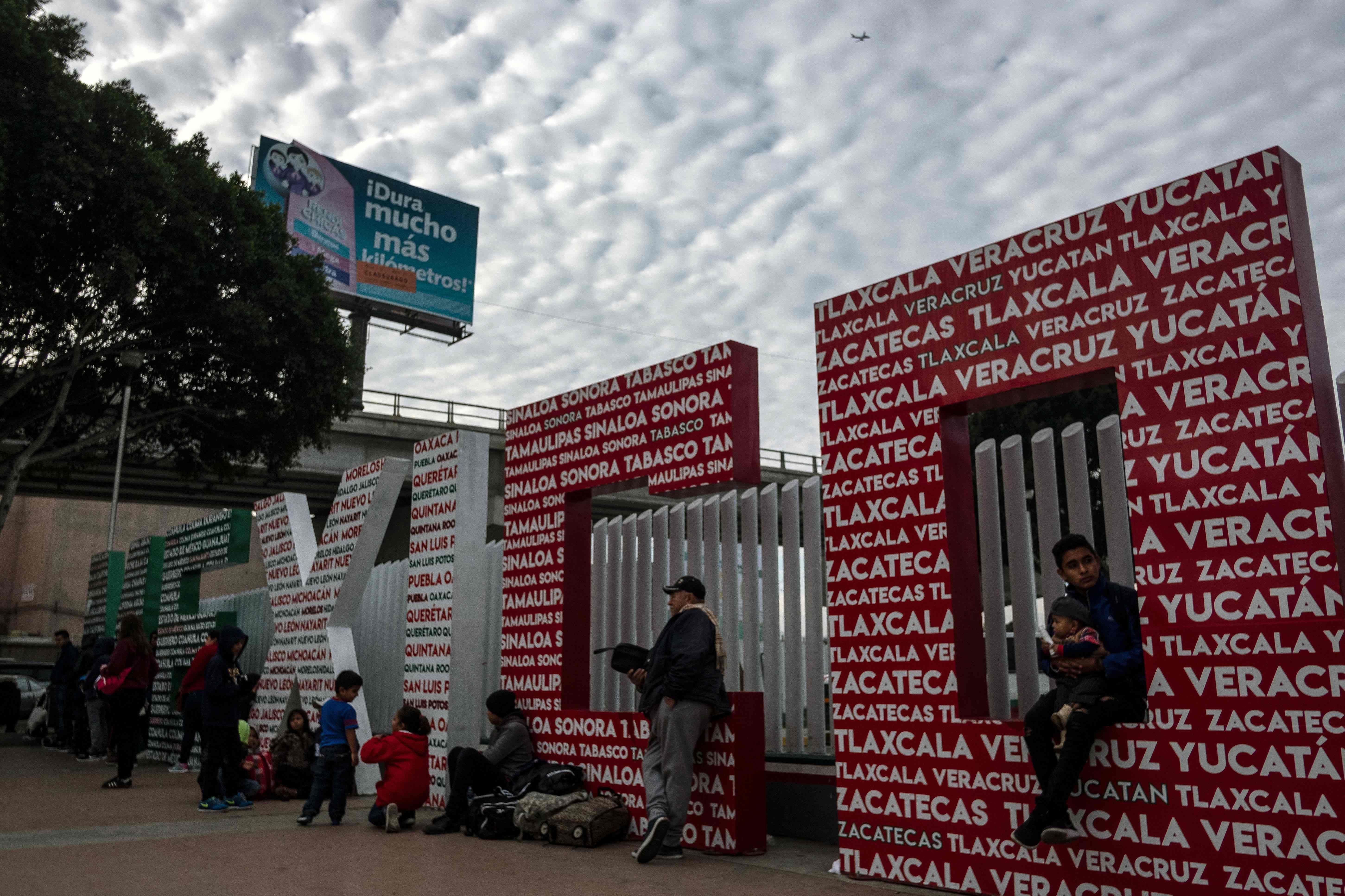 Solicitantes de asilo esperan en El Chaparral, después de cruzar la frontera en Tijuana. (Foto Prensa Libre: AFP)