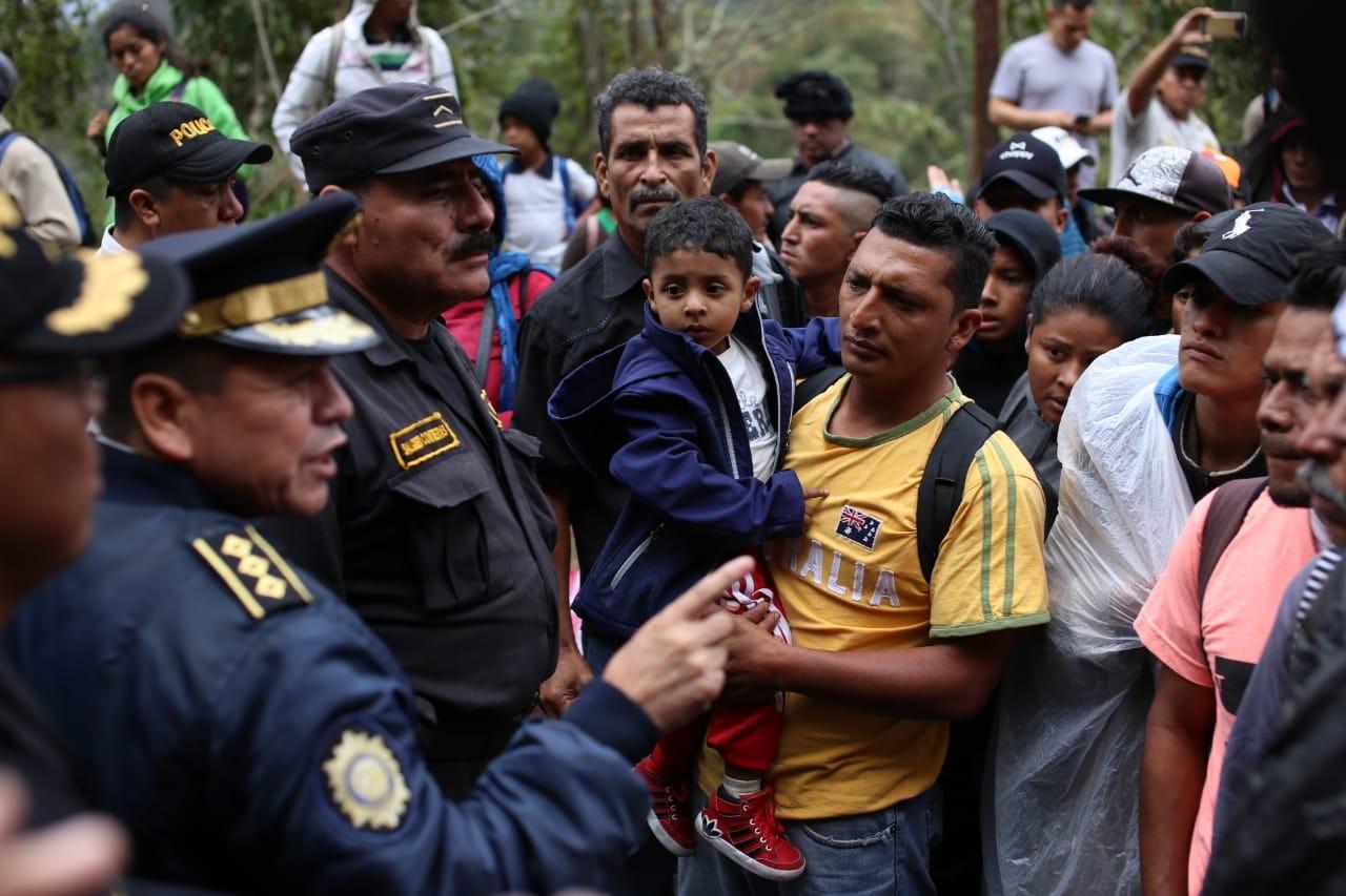 Migrantes hondureños dialogan con agentes de la Policía Nacional Civil antes de registrarse en la aduana de Agua Caliente. (Foto Prensa Libre:  Carlos Hernández)