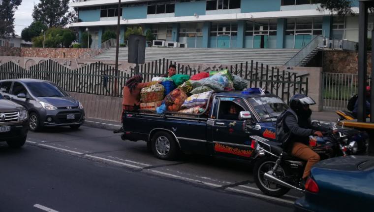 Desde temprana hora varios picops sobrecargados circulan en la ciudad y en sus palanganas transportan personas sobre la mercadería. (Foto Prensa Libre: Óscar Fernando García).