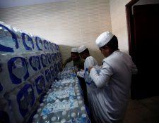 Niños musulmanes estiban cajas de agua en la mezquita de la fundación islámica Jummah Masjid. (Foto Prensa Libre: EFE)