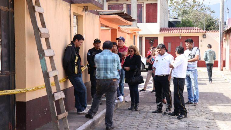 Familiares de las victimas y bomberos esperan en el exterior de la vivienda donde ocurrió el hecho, mientras el MP recolecta evidencias. (Foto Prensa Libre: María Longo)
