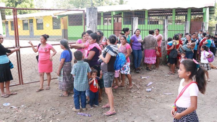 Una de las madres de familia muestra el candado que colocaron en el portón de la escuela de la aldea Morazán. (Foto Prensa Libre: Cristian Soto).