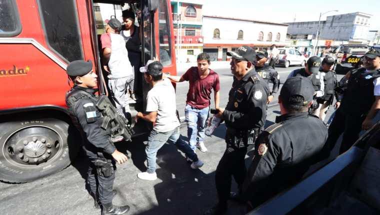Pasajeros de un autobús de la ruta 32 suben luego de ser revisados por agentes de la Policía Nacional Civil en un retén en la 9 calle y 11 avenida, zona 7. (Foto Prensa Libre: Óscar Rivas)