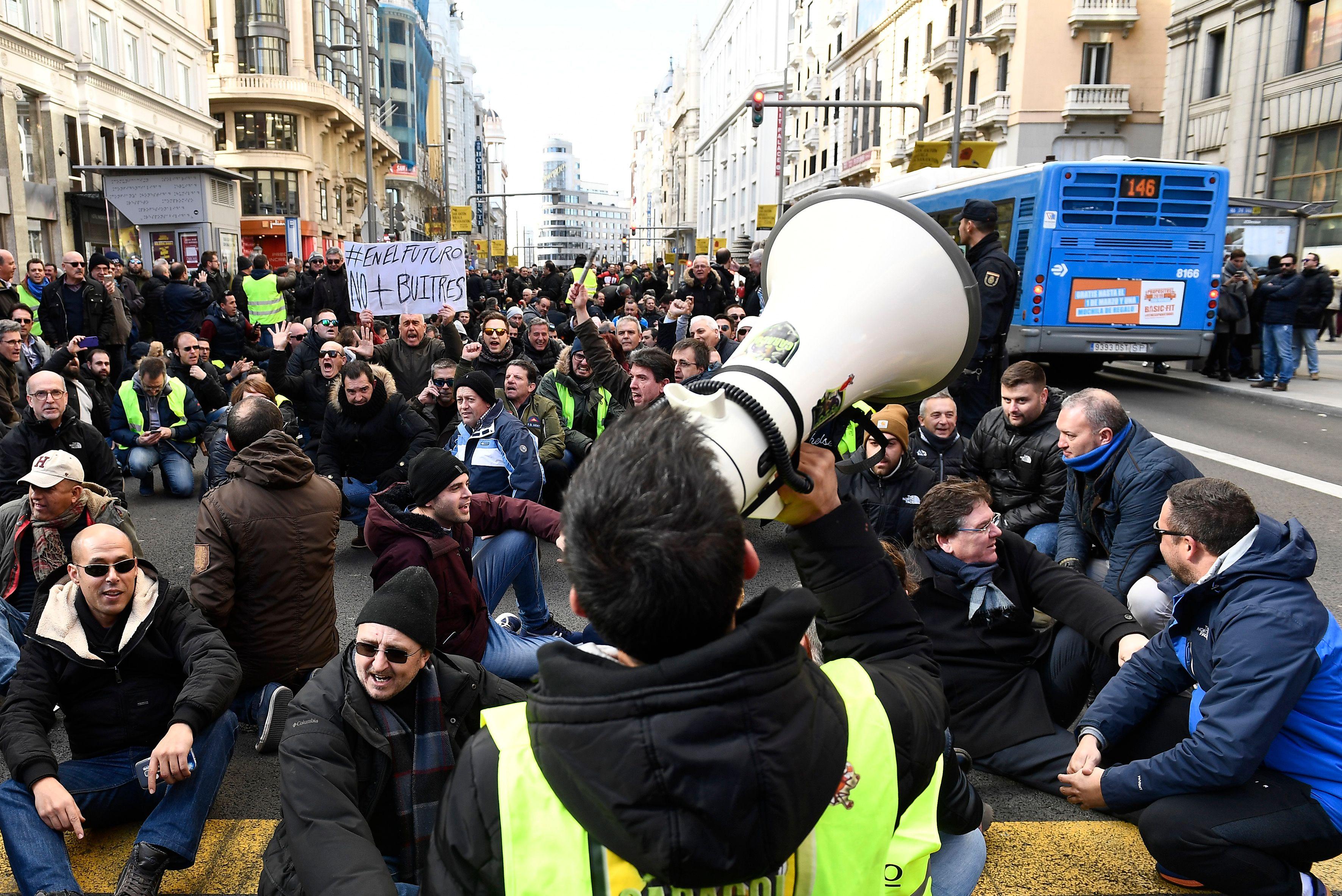 Los taxistas se sientan en la calle Gran Vía de Madrid durante una manifestación el 21 de enero de 2019 para protestar contra los reglamentos propuestos por las autoridades para los VTC (vehículos de turismo con chofer). (Foto Prensa Libre: AFP)