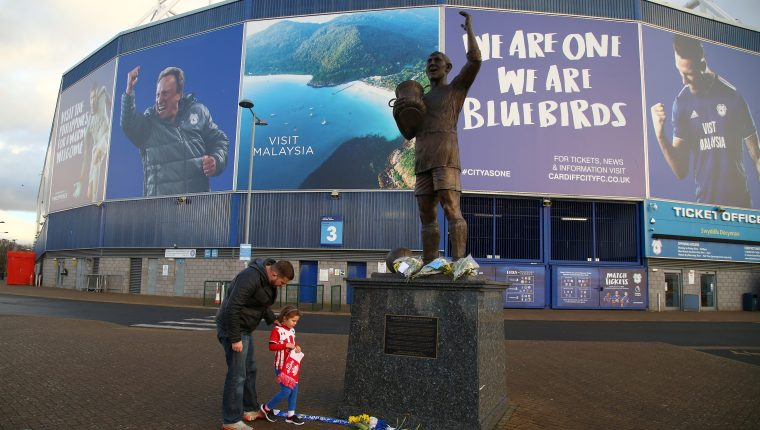 People place a Southampton scarf alongside bunches of daffodils and Cardiff City scarves at the foot of the statue of Fred Keenor, outside Cardiff City's football stadium in Cardiff, south Wales on January 22, 2019, after news of the disappearance of the plane carrying their new signing Emiliano Sala breaks. - French civil aviation authorities confirmed today that newly-signed Cardiff City striker Emiliano Sala was on board a light aircraft feared missing off the Channel Islands. (Photo by GEOFF CADDICK / AFP)