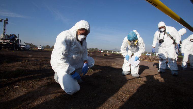 Expertos forenses registran la zona cerca de una toma clandestina de gasolina de Petróleos Mexicanos (Pemex). (Foto Prensa Libre: EFE)