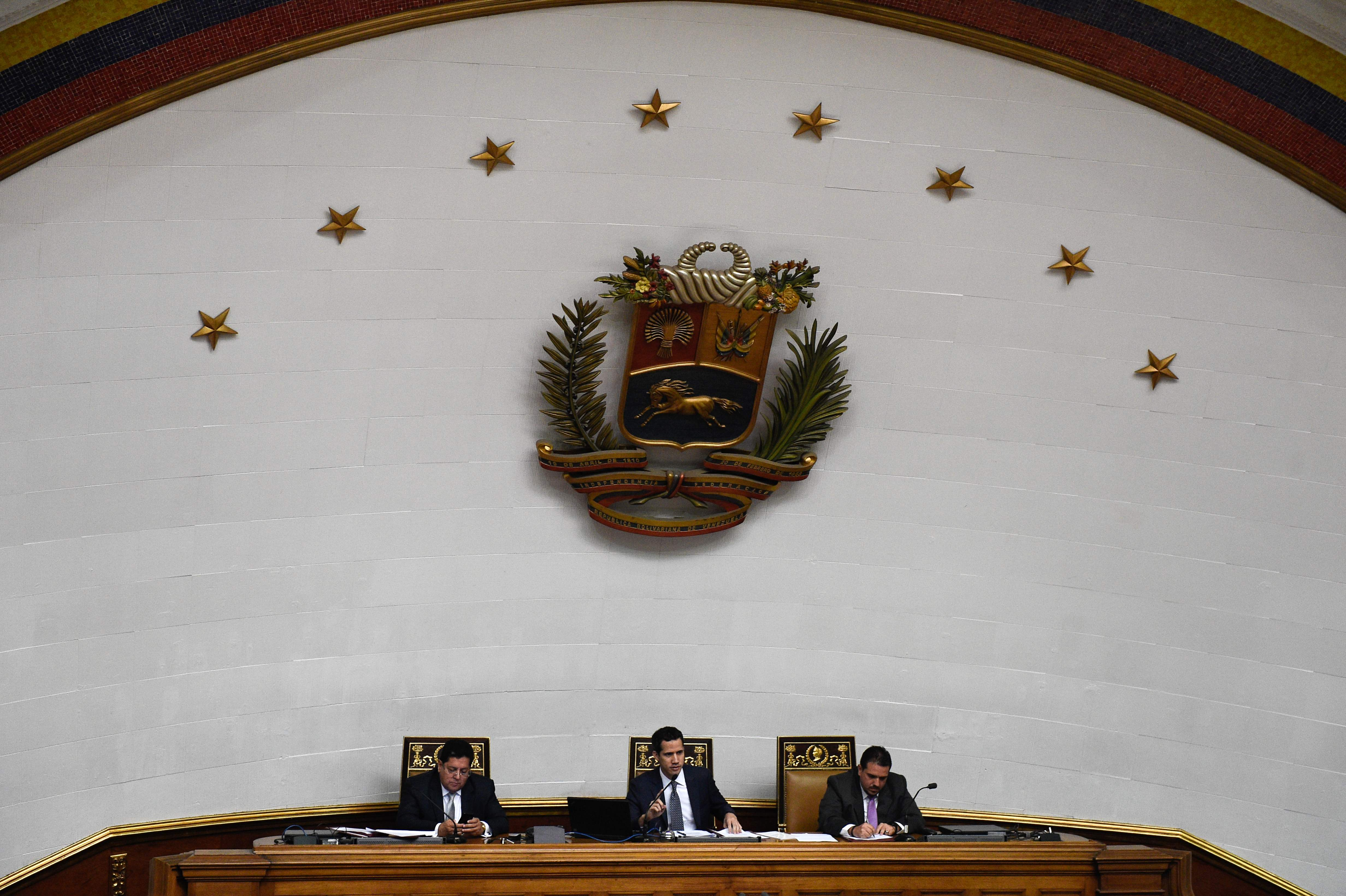 "Venezuela's National Assembly president Juan Guaido (C), first vice president Edgar Zambrano (L) and second vice president Stalin Gonzalez (R) attend a session at the Federal Legislative Palace in Caracas on January 22, 2019. - Venezuela's Supreme Court declared the leadership of the opposition-controlled National Assembly illegitimate and its decisions ""void"" Monday after it repudiated the presidency of Nicolas Maduro. (Photo by Federico PARRA / AFP)"